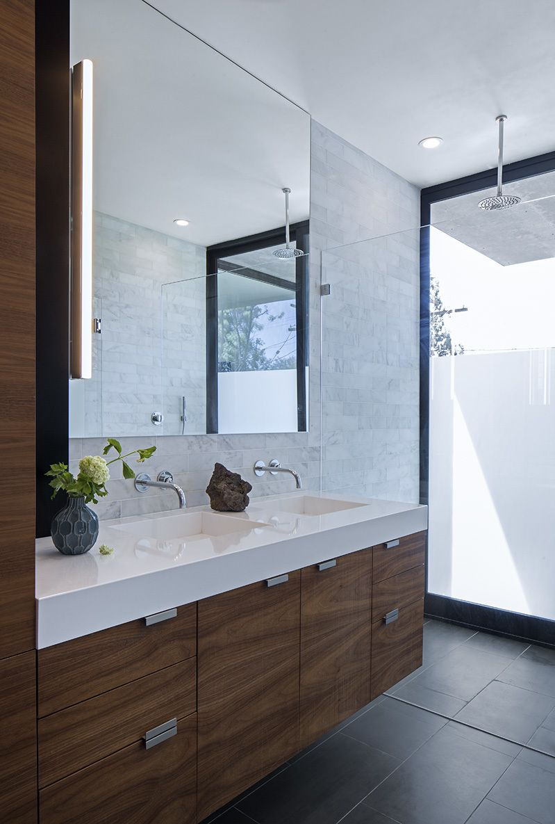 Silestone counters, walnut cabinetry, and Refin floor tiles accent the  master bathroom. The Axor Uno faucets are from Hansgrohe, the Alinea vanity  light is ...