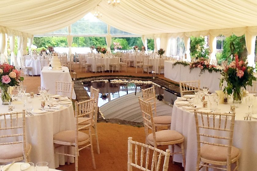 Real marquees light and pretty wedding marquee in east grinstead east sussex with a pond in the middle and open sides