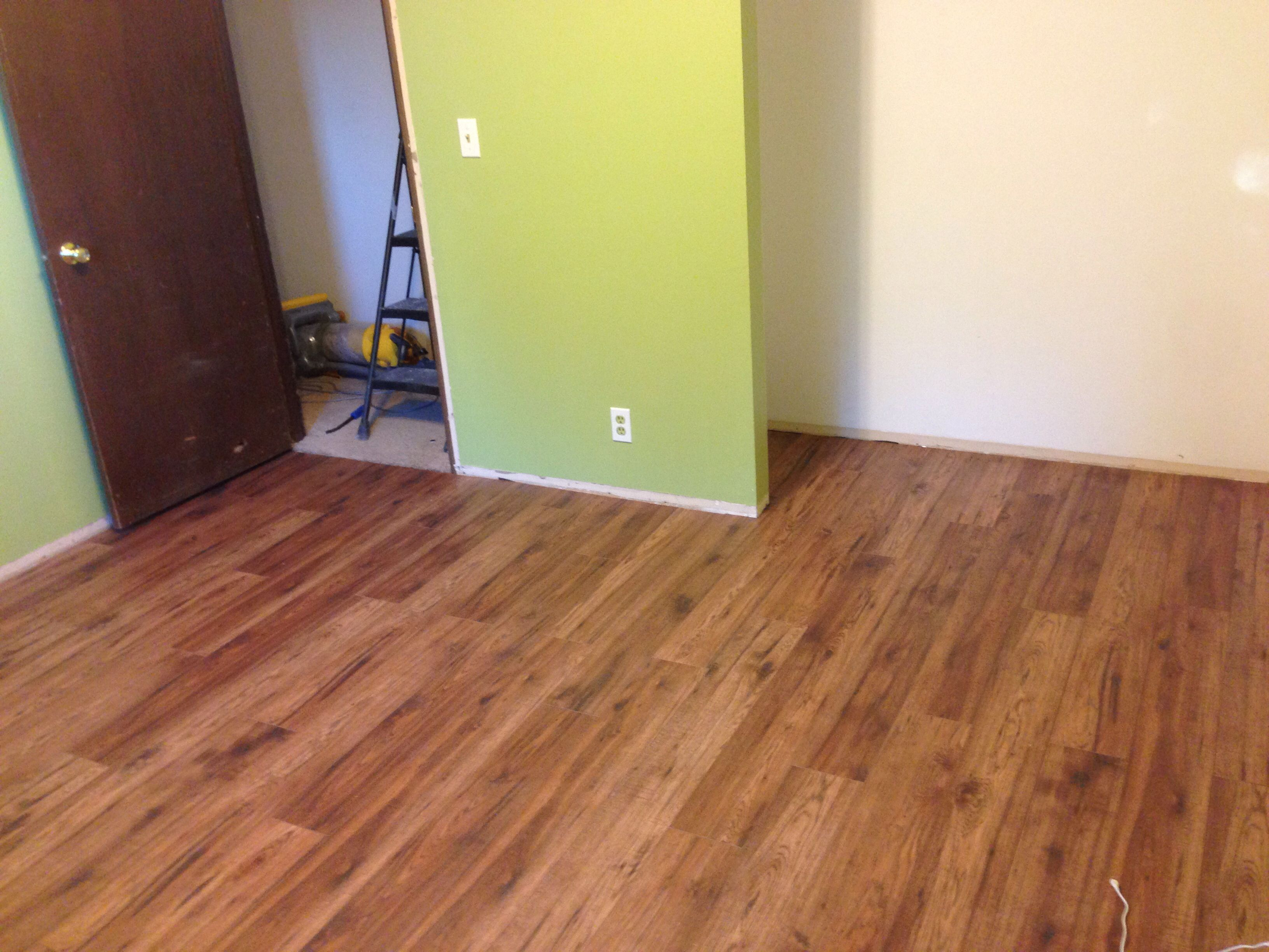 Distressed brown hickory pergo flooring and Behr s Asparagus paint