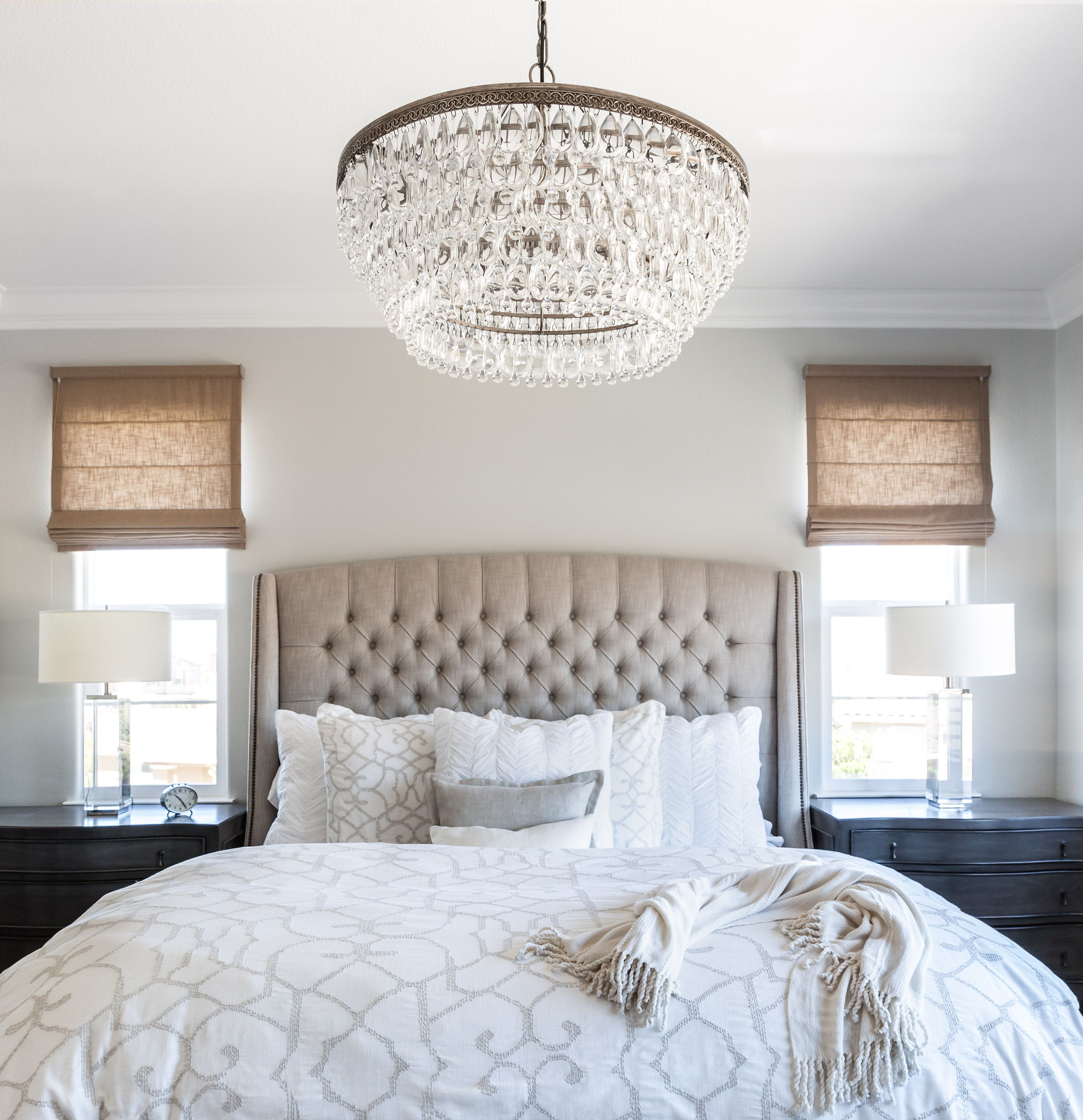 master bedroom linen bed roman shades cream bedding calming master bedroom gray walls tufted headboard crystal chandelier designer juxtaposed - Bedroom Chandelier