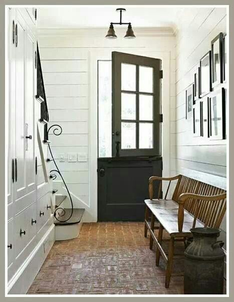 This is simple compact hallway. I like the cupboard. Bench is very practical in hallways.  Pot for umbrella is adding interest. We can see vertical lines on bench. Glass door has vertical and horizontal lines. Natural light is making that hall way open and bright. Beautiful railing curve is adding interest.