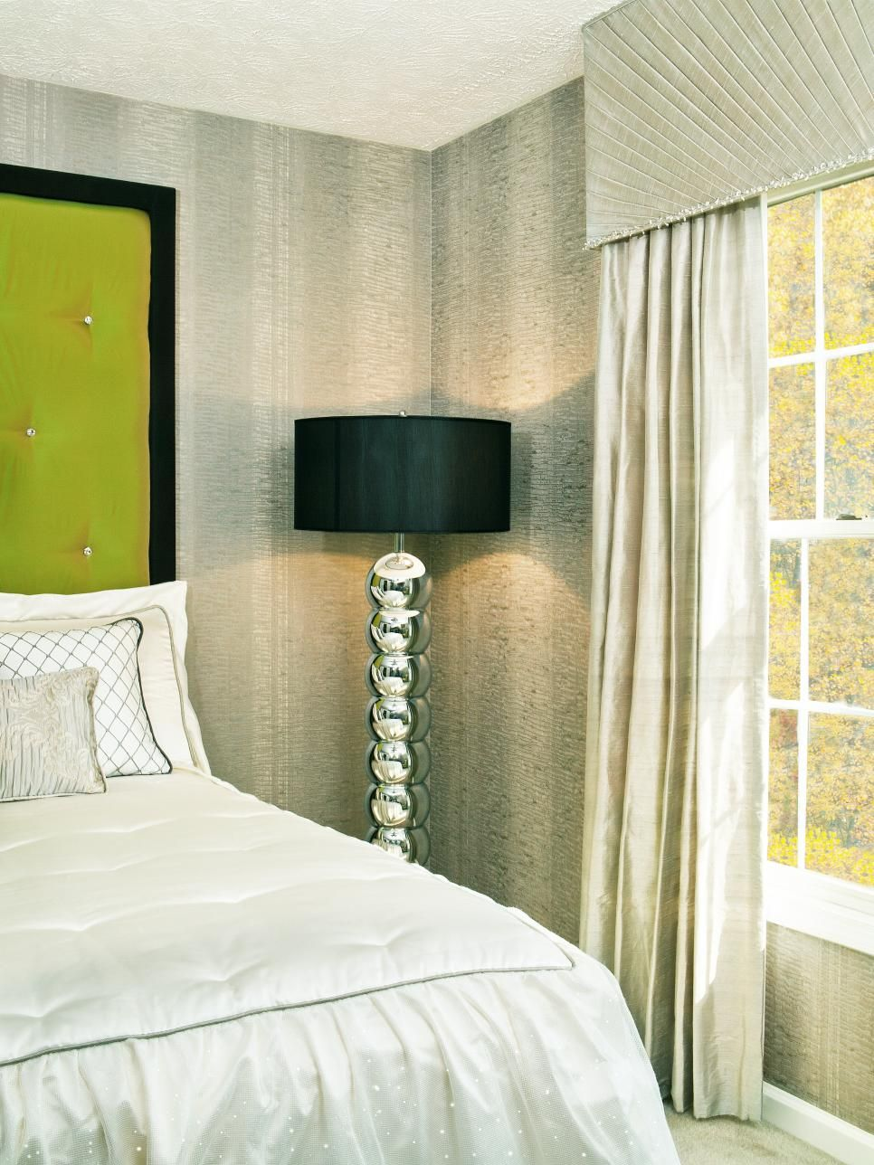 Subtly striped wallpaper and a tall metallic floor lamp add visual depth to this art deco-inspired guest bedroom. Custom touches including a green tufted upholstered headboard and combination comforter/dust ruffle help make the neutral space an ideal feminine retreat for the homeowner.