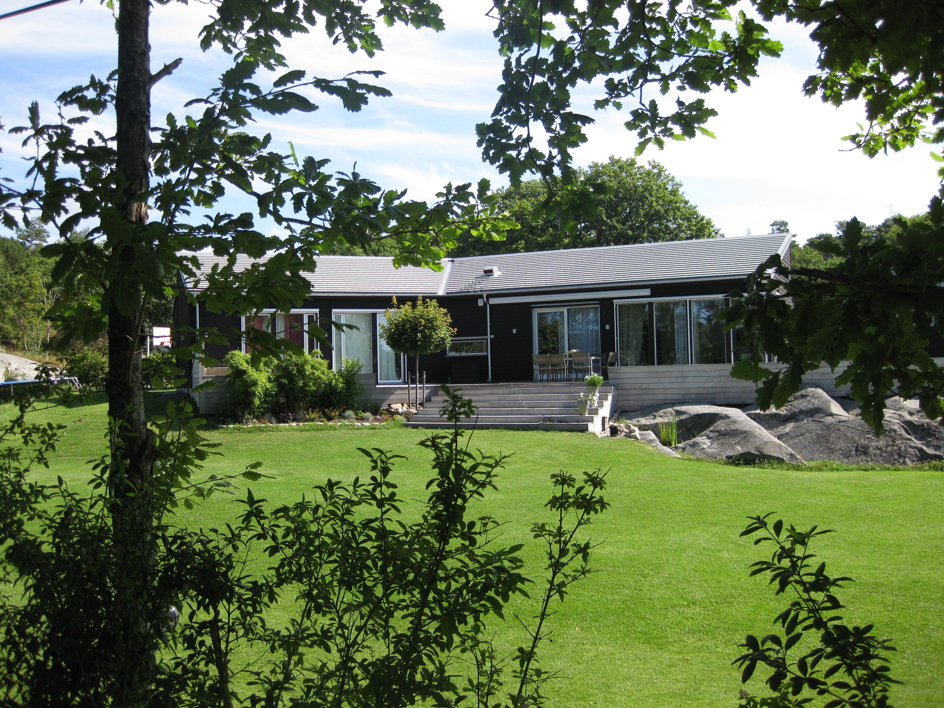 this is a seaside house in Sweden. Like the colour scheme with black cladding, and silver decking.
