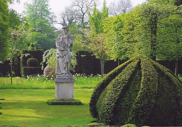 The Garden at Highgrove - One of the Italian statues which stands in a break in the rows of pleached hornbeams lining the Thyme Walk. The swaggered yew hedge beyond encloses a spring display of bulbs and blossom.