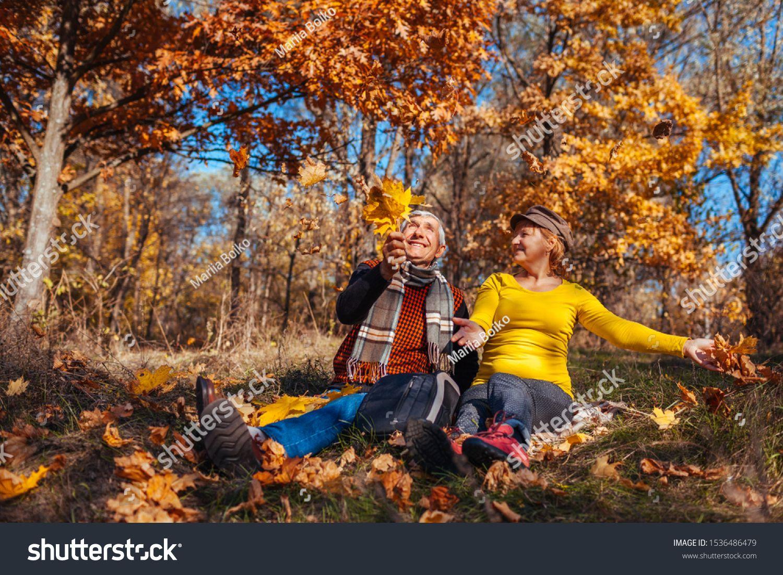 Autumn season fun. Senior couple throwing leaves sitting in park. Man and woman ...