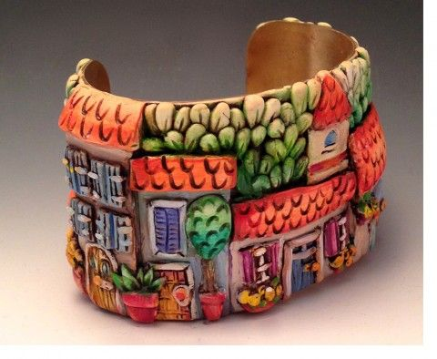 Our first guest blog partner is Ginger Davis Allman, blogger extraordinaire at The Blue Bottle Tree and creator and author of numerous techniques and tutorials. She brings us, normally known for her whimsical and cartoon-like character sculptures, Doreen Kassel also makes jewelry with the same recognizable fun and engaging style. This cuff bracelet features a sculpted street scene reminiscent of a quaint rural French village. The Polymer Arts magazine - Go to www.thepolymerarts.com