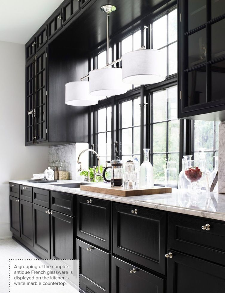 Black cabinetry topped off with white marble