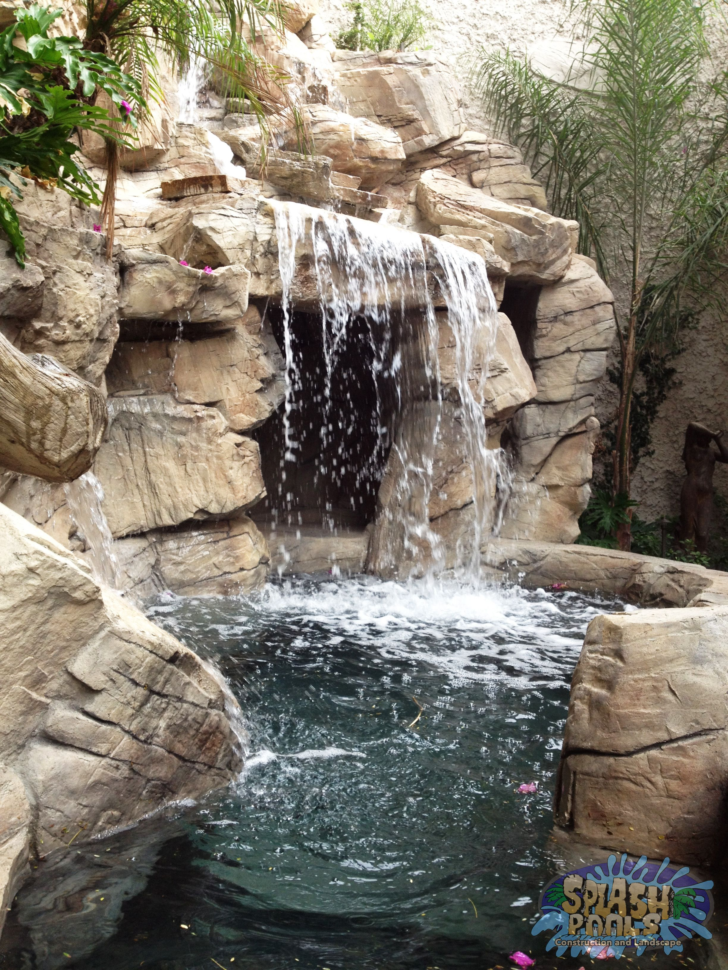 Custom rock spa in a small backyard with waterfall splash for Swimming pool waterfalls construction