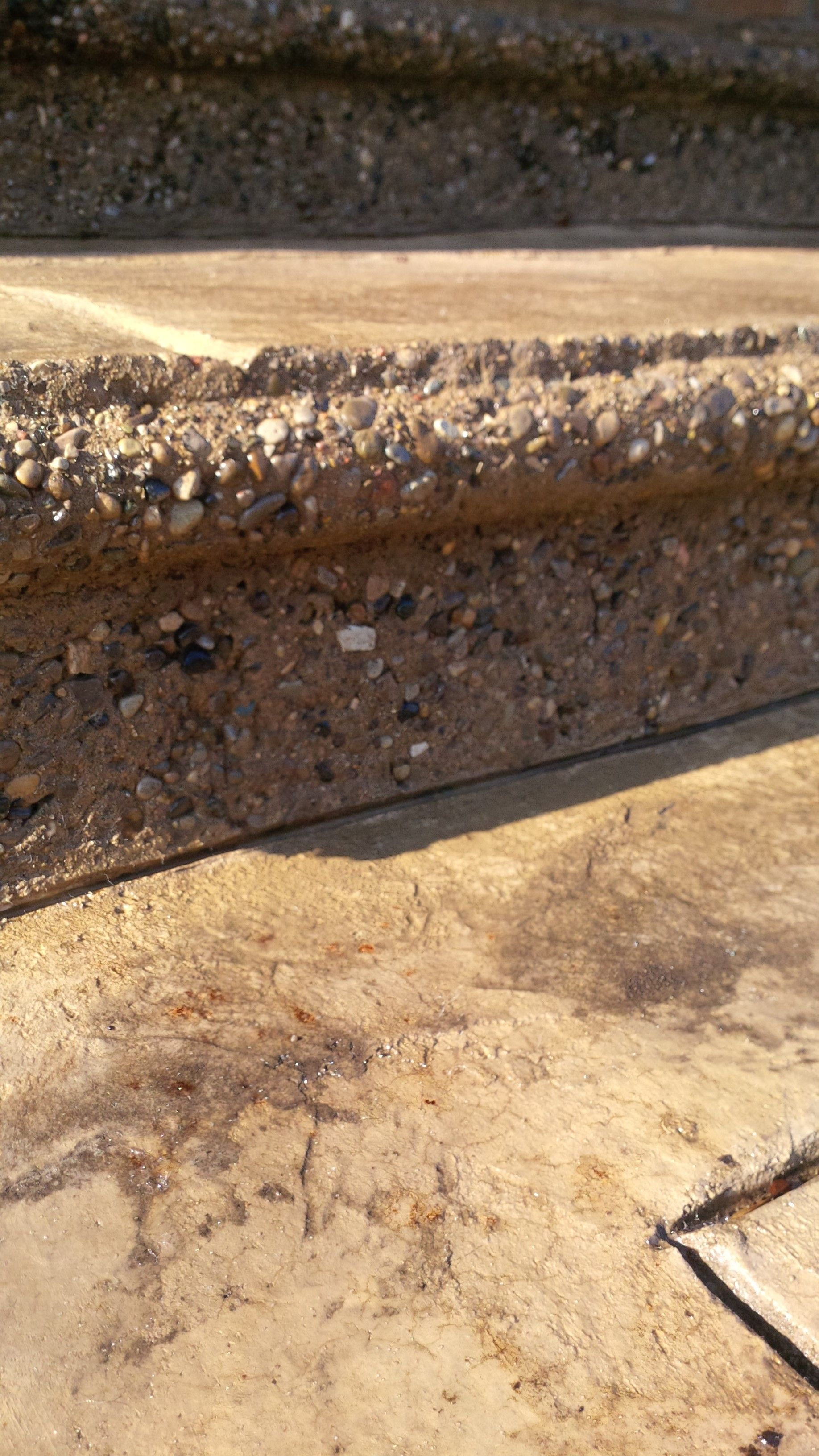 front view of a stamped and exposed aggregate concrete step.