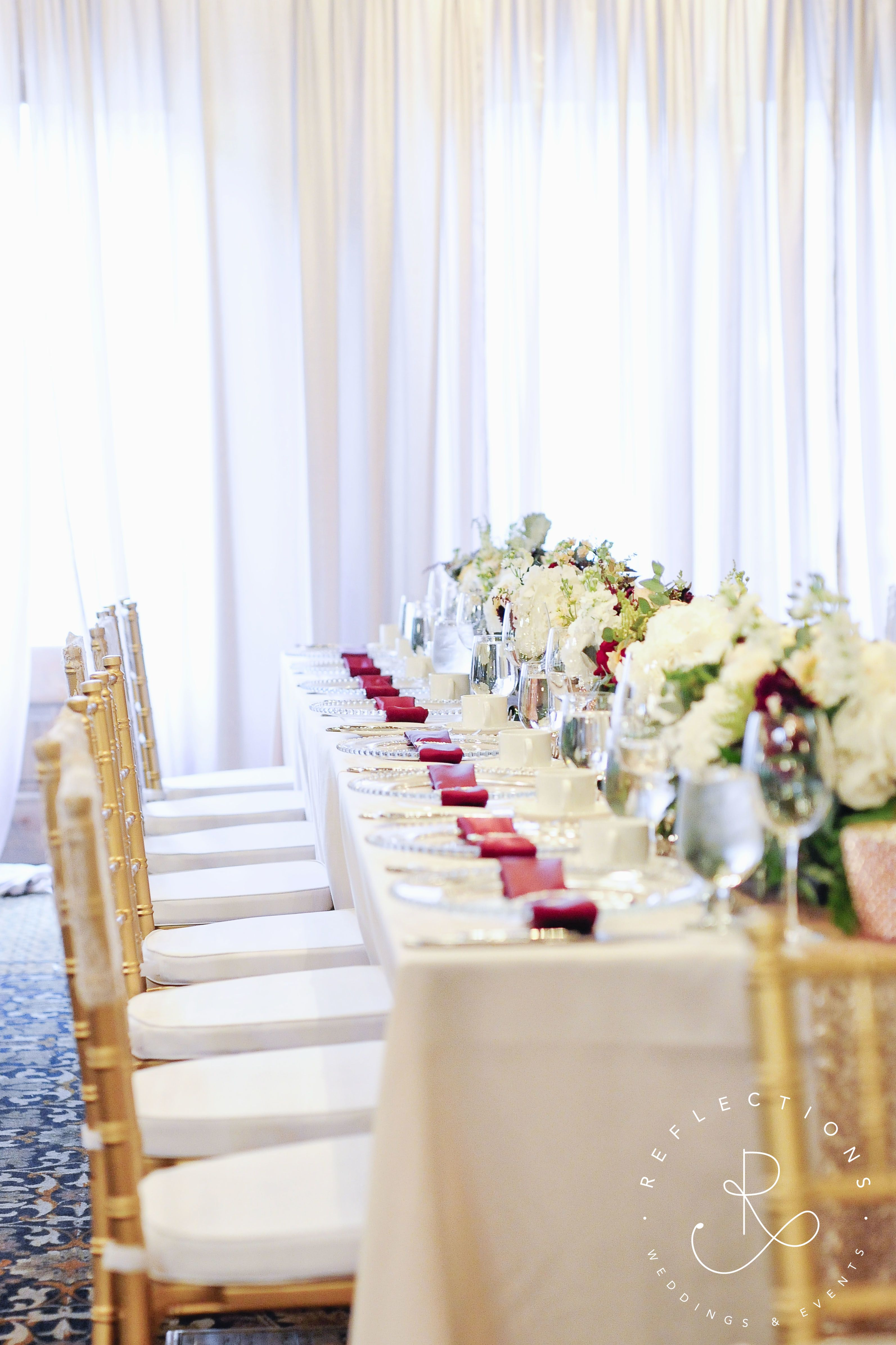 Ivory, blush, gold and burgundy wedding decor on long banquet table ...