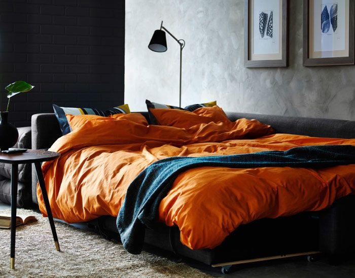 A living room with a corner sofa-bed made with orange quilt cover ...