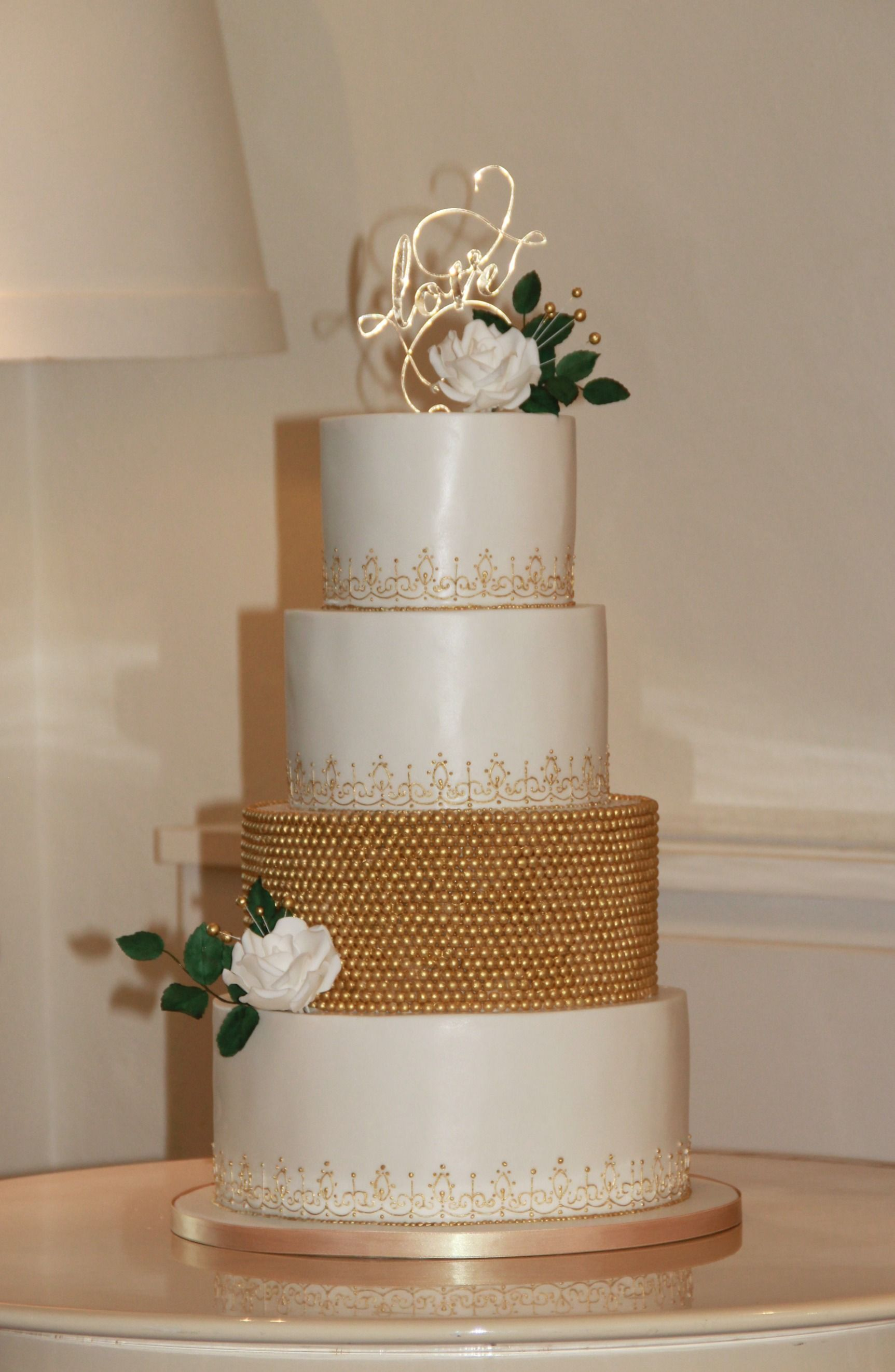 White and gold 4-tiered cake with gold sugar pearls and ...