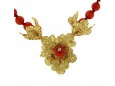 Collana realizzata in oro giallo con la tecnica della cera persa, arricchita da corallo rosso e da un diamante.