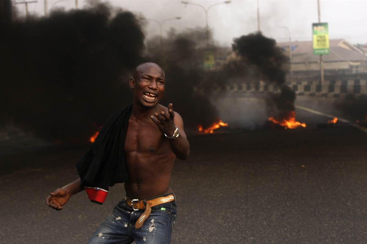 Fury over fuel    An angry youth protests in front of a burning barrier following the government's decision to do away with a fuel subsidy that kept gas prices low, Jan. 10 in Lagos, Nigeria. Protesting youths erected a burning roadblock outside luxury enclaves in Nigeria's commercial capital as part of a paralyzing national strike over fuel prices and government corruption.