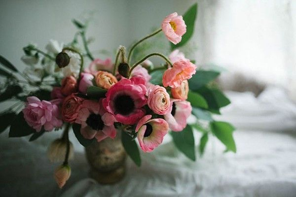 loose wedding centerpiece with pink flowers including ranunculus and anemones