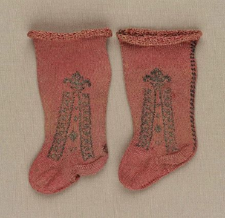 Infant's salmon pink knitted silk stockings with gilt-metal fleur-de-lis headed clocks, Italian, 1650-1750.
