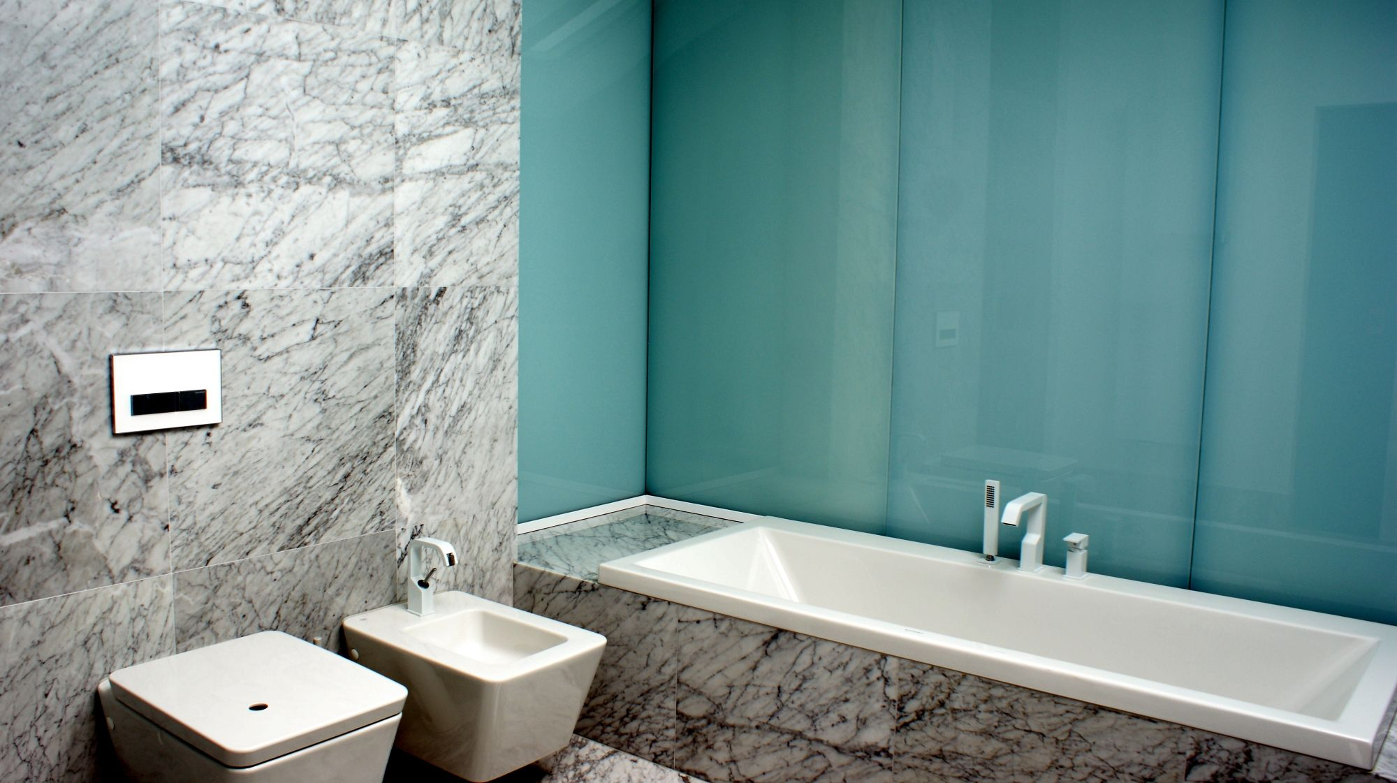 An example of a modern, minimalist bathroom with colored glass on ...