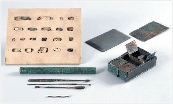 Oculist's kit from the necropolis of La Favorite in Lyon.  Brass sheet box containing twenty dried collyria (displayed) shown open with its lid on the right; beveled slate plate to grind the collyria; sheath made of two brass cylinders fitting into each other, containing the three brass instruments displayed. Dated end 2nd to beginning 3rd century AD.  © Musée galloromain de Lyon-Fourvière.