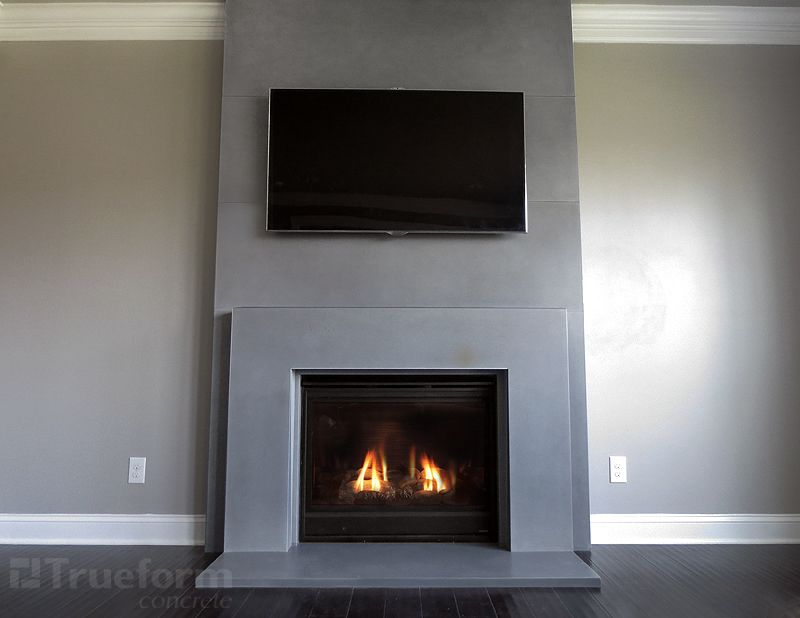 This is a contemporary gas fireplace surround cast in concrete. by Trueform concrete