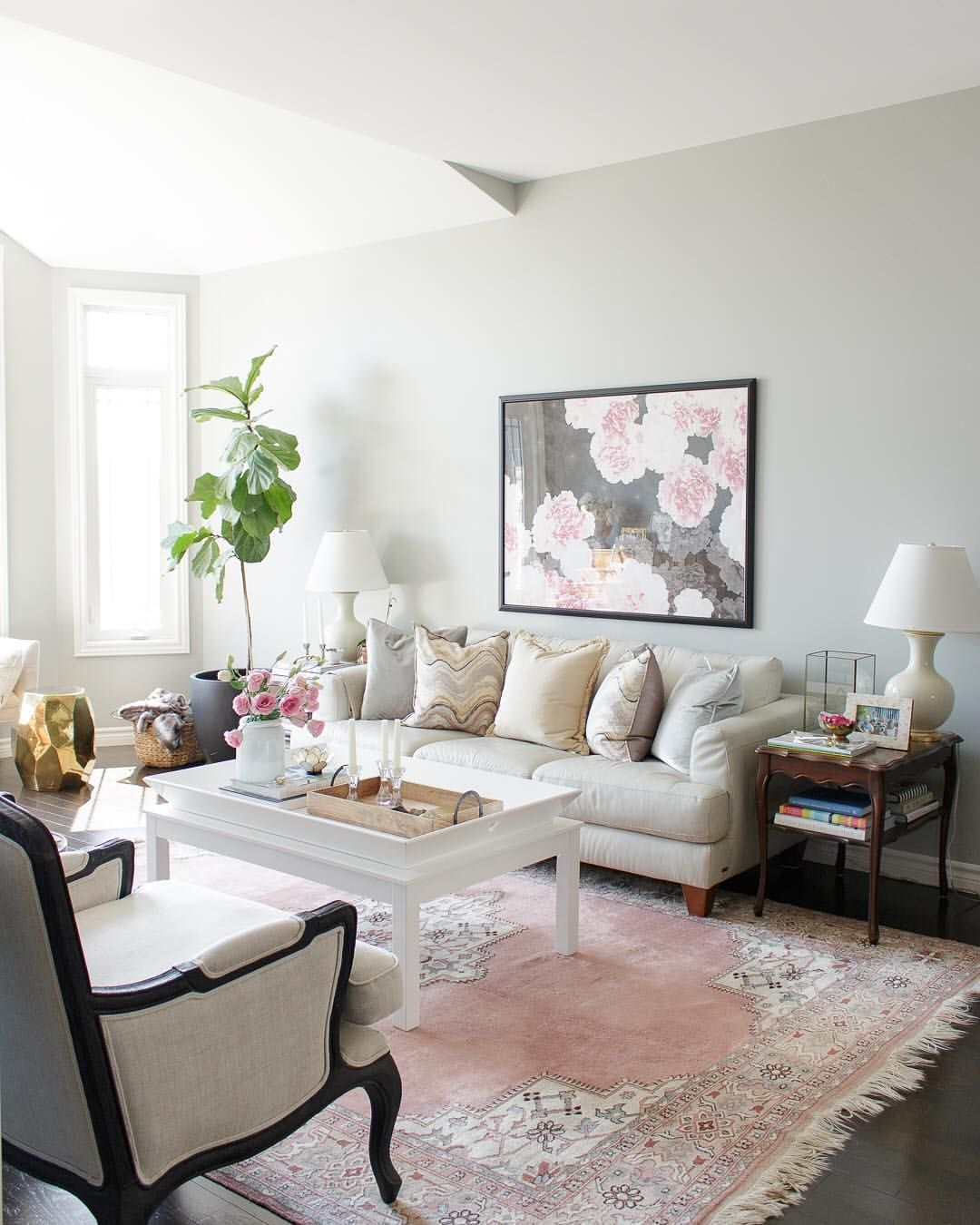 Living room with pink rug, marble print pillows and white couch ...