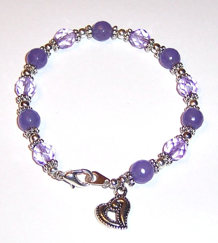 Bracelet with purple crystals, faceted purple jade, silver spacers and a heart charm.