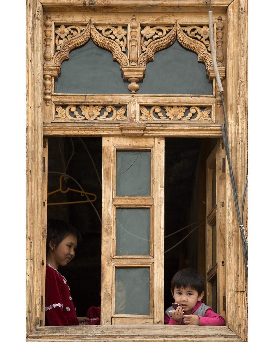 """Three curious residents peer through an ornately carved traditional wooden window in Kashgar's old town. Can you spot the third face ?"""