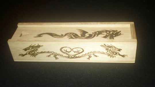 Woodburnt design on a wooden pencil case.