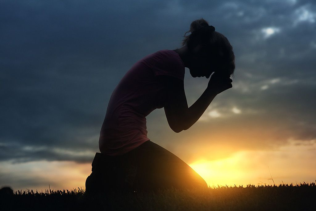 A woman prays on her knees at sunset. | Woman praying images, Kneeling in prayer, Prayer images