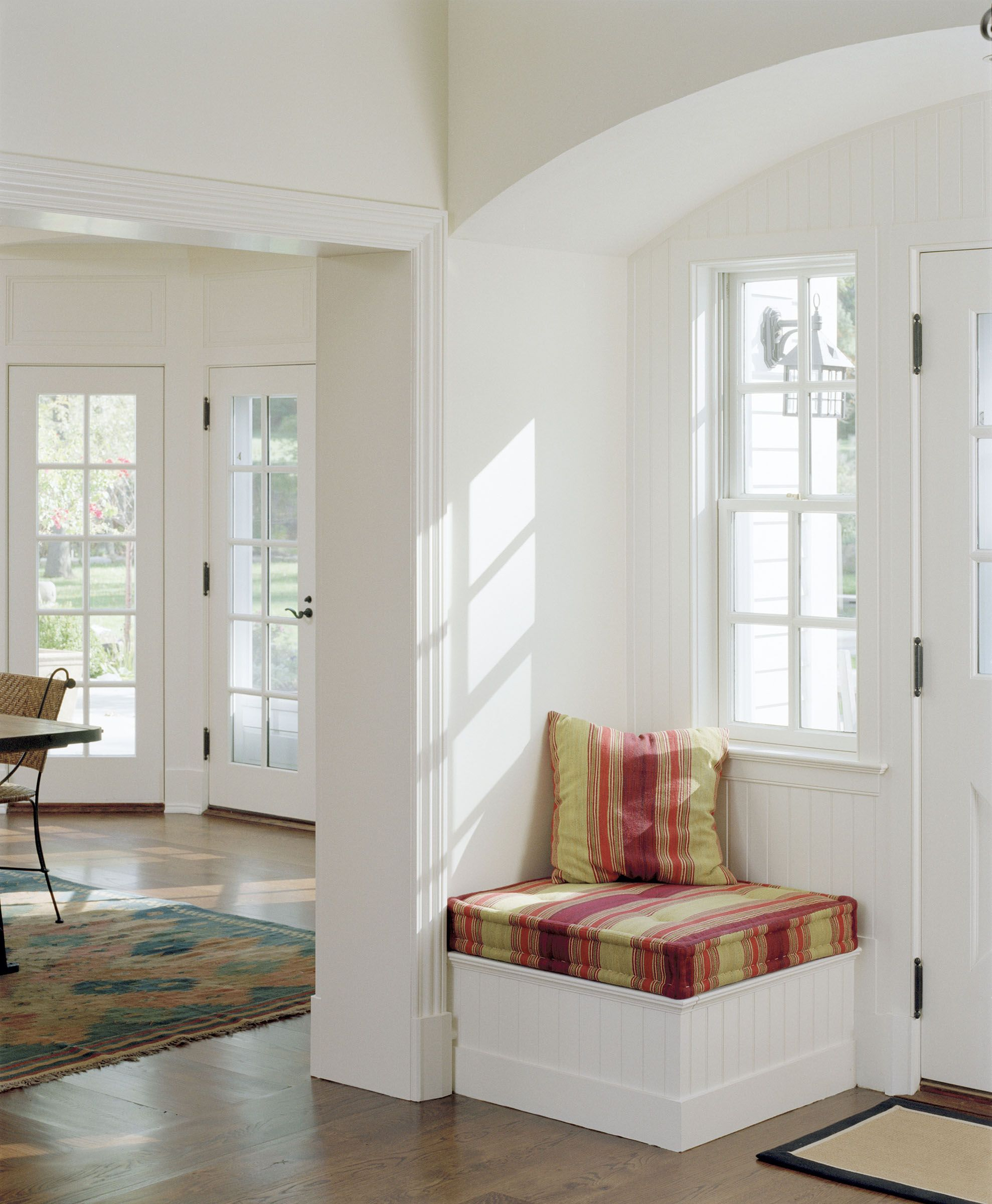 A Small Seat Under Window Next To The Front Door Is Decorative And Practical