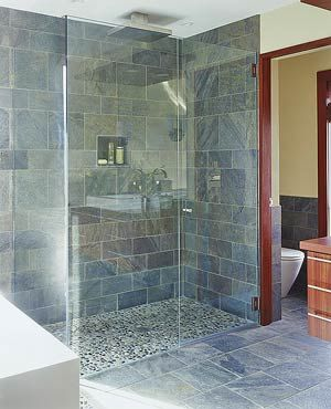 A Rain Style Showerhead Gl Enclosure Minimizes Splashing From The Pebble Floor And Slate Wall Tiles River Stones Are Used In Shower