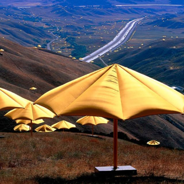 Artist Christo planned for more than 1,700 giant yellow umbrellas to flutter open on the barren, tan slopes of the Tejon Pass north of Los Angeles, completing one of the largest undertakings in modern art history. (1991)