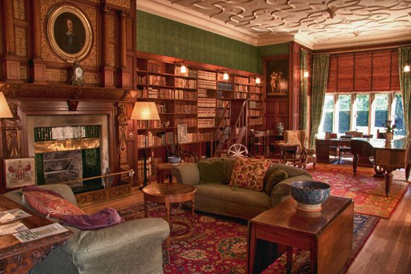 The library at Kiplin Hall in North Yorkshire, England. The house was first built in the 1620s, but major additions were made in the 1720s, 1820s and 1890s, when the library was made. In 1887, William Eden Nesfield transformed the drawing room into a handsome, Jacobean-style library, with dark oak paneling, a fireplace with tiles by William de Morgan and an ornate plaster ceiling. The painting above the fireplace is Charles I.