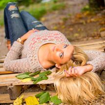 2014 senior, Maddie, lays on a wooden pallet in an alley surrounded by leaves.