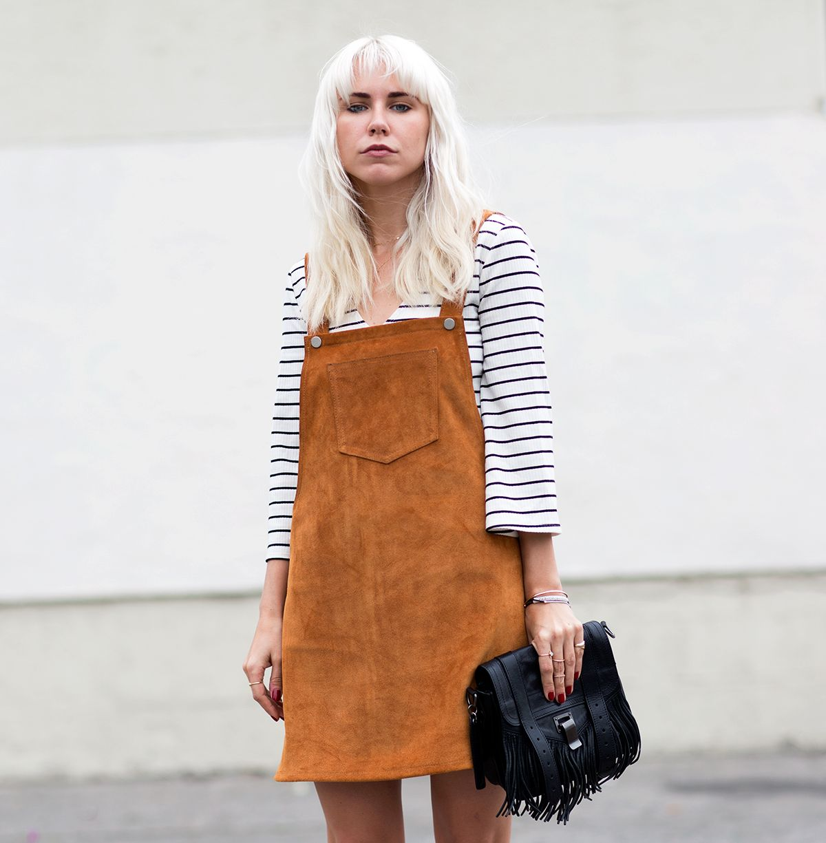 Suede overall dress with a striped tee and Proenza clutch.