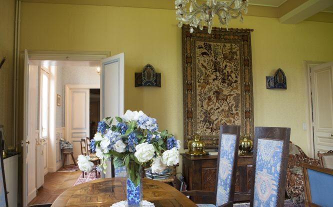 tapestry on yellow walls with blue damask fabric and china vase