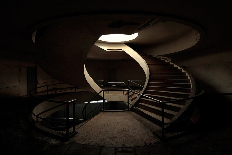 Double spiral staircase in an abandoned office building in France, by Le Luxographe