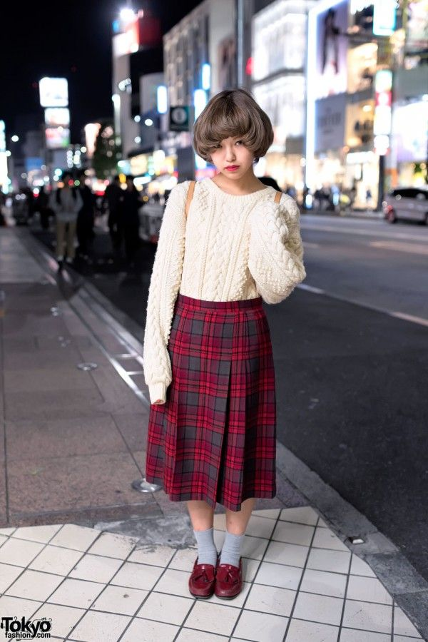 Mana is a Japanese high school student with a cute retro hairstyle and vintage aesthetic. Her look features an oversized cable knit sweater with extra-long sleeves, a pleated plaid midi skirt, gray socks, and maroon tassel loafers. Her bag choice is a small leather LV backpack. She likes the music of Shinee.