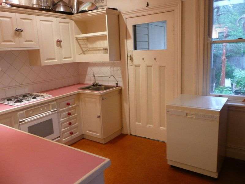 Pink Laminate Countertops. Rusty Old Appliances Including Floating  Dishwasher.