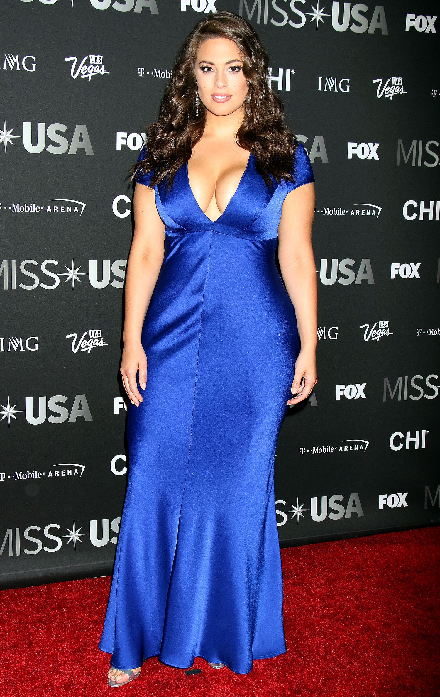 ASHLEY GRAHAM in a low-cut blue gown, plus silver sandals and diamond  jewels, at the Miss USA competition in Las Vegas.