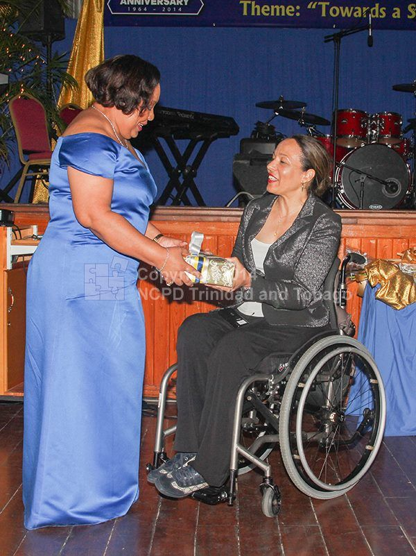 Chalotte McClain-Nhlapo receiving at token from Dr. Beckles, CEO of NCPD.