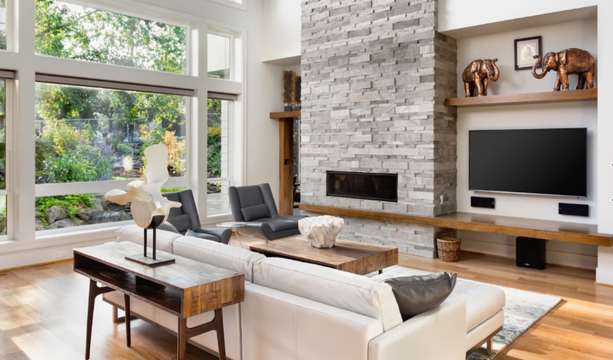 Living room with stone fireplace with TV next to it ...