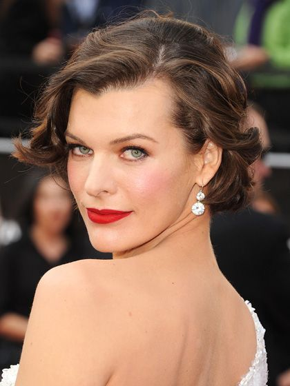 Milla Jovovich wavy updo with side-swept bangs, red lipstick and pink blush