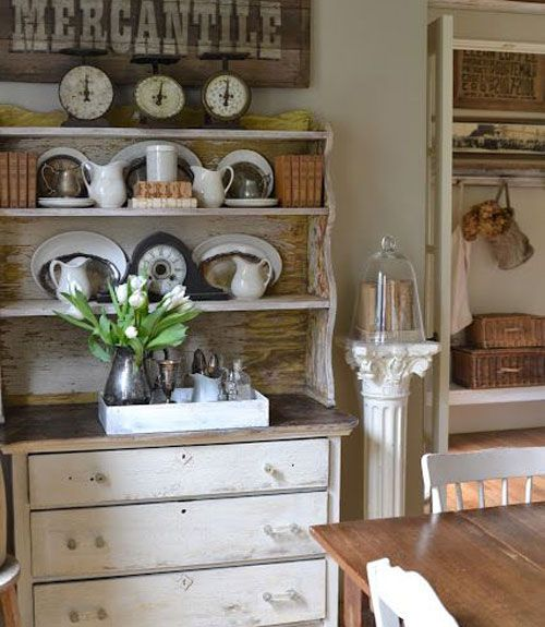 A Weathered Sign Hangs Above The Dining Room Hutch, Which Displays A  Collection Of Vintage