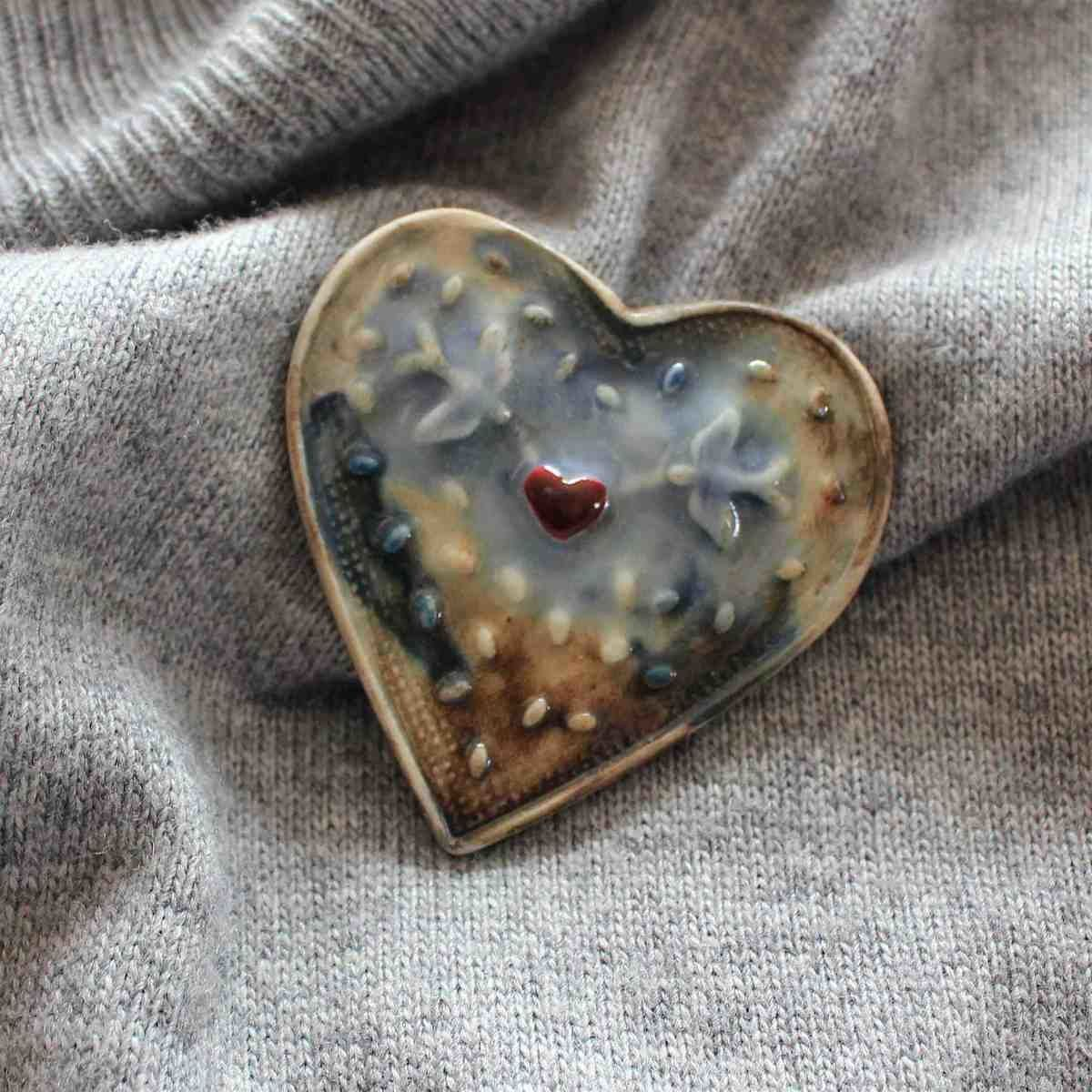 Country Living Editor Says  Made from porcelain, with oxide and glaze decoration, this heart-shaped brooch will add a distinctive touch to any outfit.  Each one is handmade so there may be slight variations, making every piece charmingly unique.   Measurements: 5cm x 5cm at widest points.