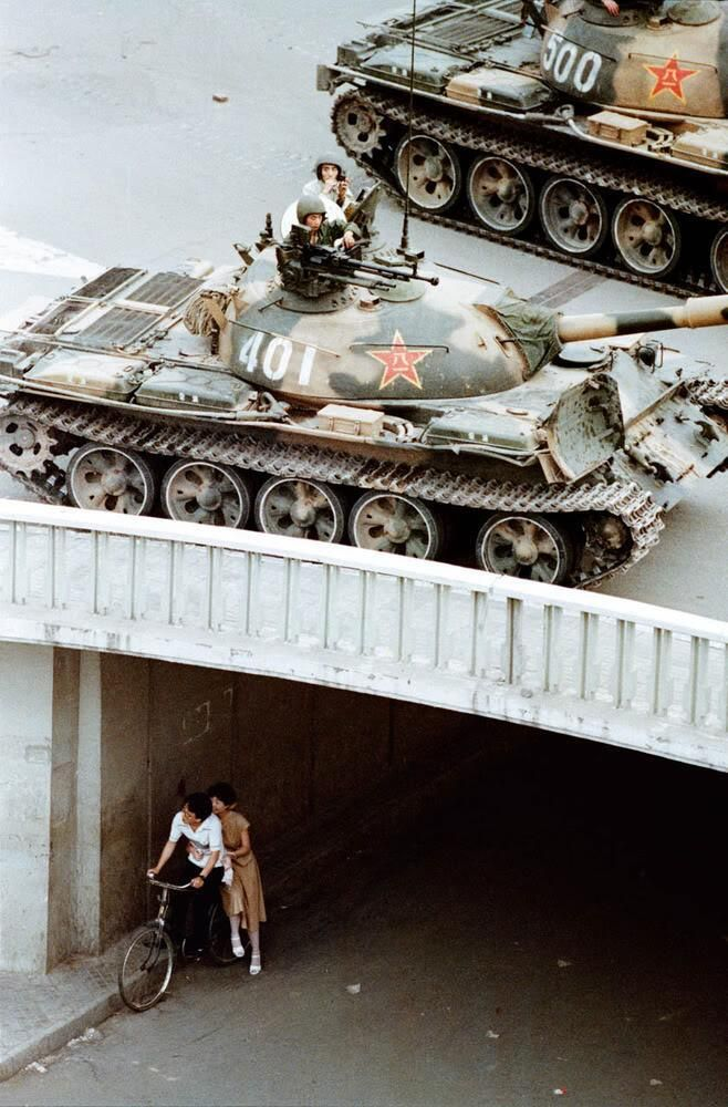 A young couple waits beneath Jianguomenwai Bridge as PLA tanks pass above them in China on June 5th, 1989.