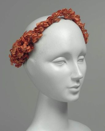Woman's headdress, French, worn in Boston, mid-19th century. MFA, 52.1267. Woman's headdress or wreath of red-orange artificial flower blossoms; wire circle around head wrapped in red-orange silk thread, clusters of flower blossoms in same color on thin silk-wrapped wire stems, three thin strips of gilt paper at the center of each blossom.