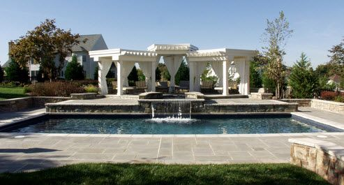 Resort-style pool with a waterfall and pergolas.