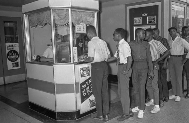 Civil rights activists line up at the ticket window of the