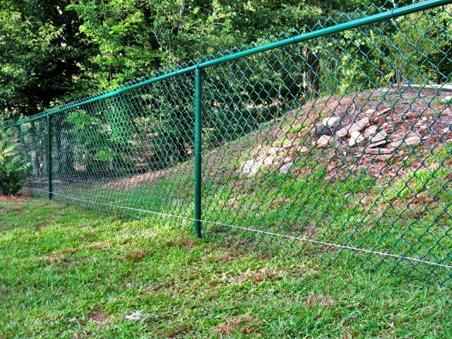 Green Vinyl Coated Chain Link Fence with a Tension Wire along the ...