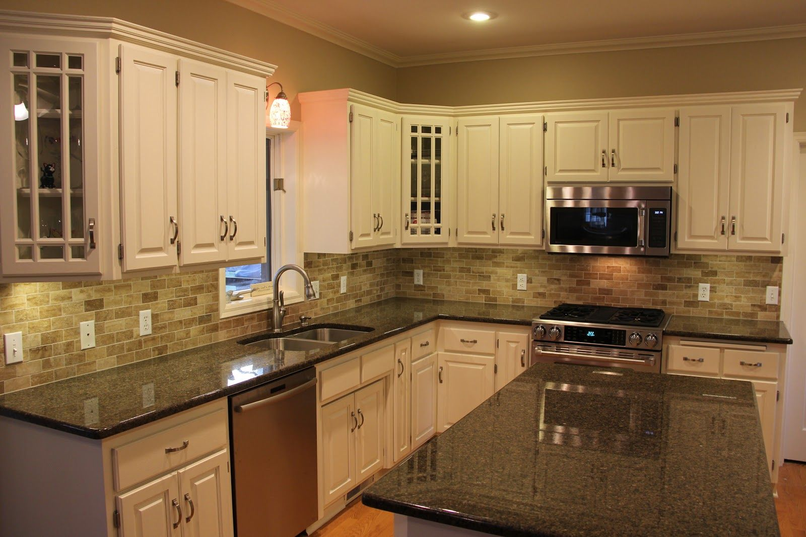 Black kitchen granite countertops with tile backsplash and